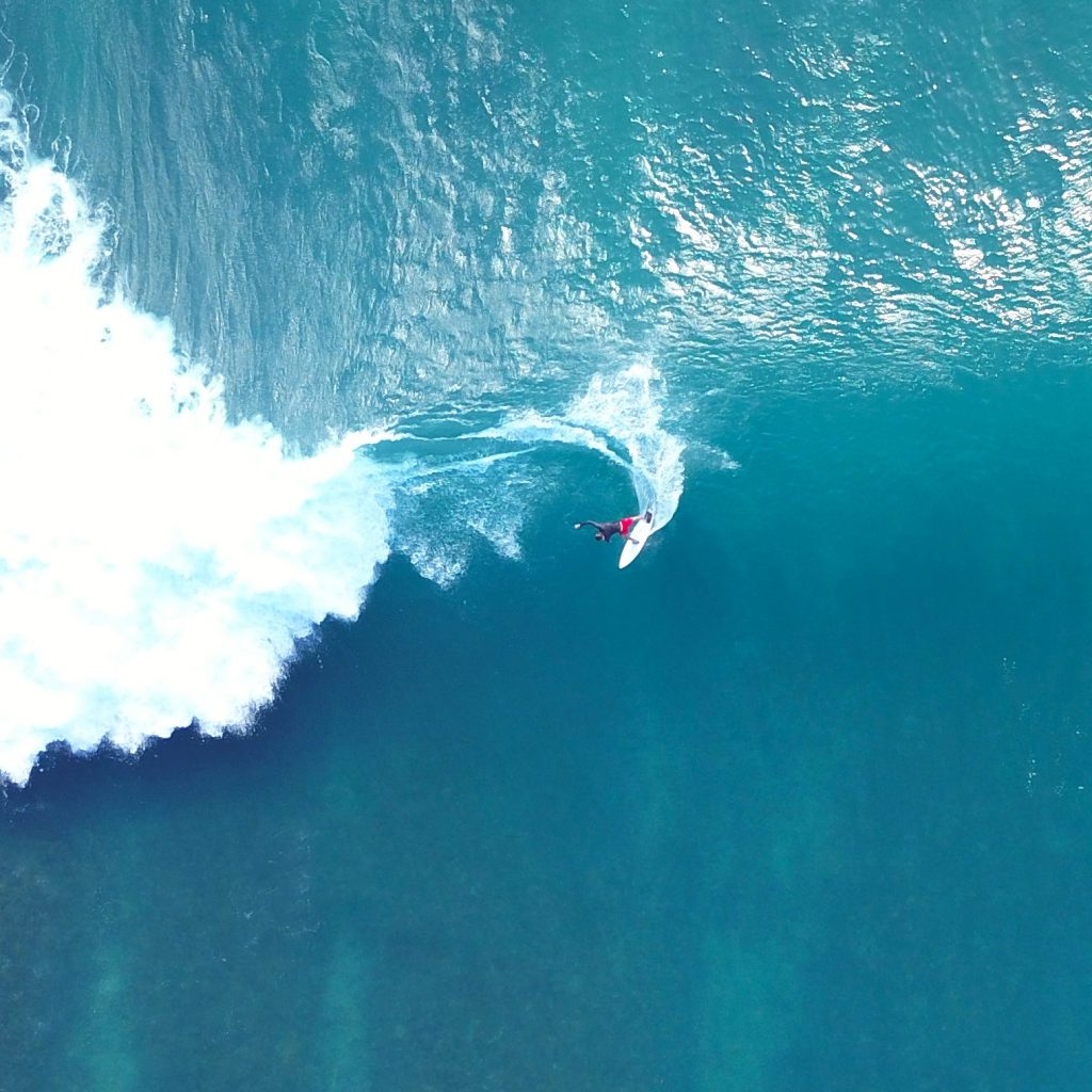 AERIAL, TOP DOWN: Unrecognizable pro surfer riding a stunning blue ocean wave in the beautiful tropical sun. Flying over breathtaking breaking waves and extreme surfer carving them on fun surfboard.